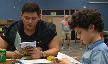 """""""Djemtë dhe librat"""", lojtarët e futbollit amerikan mësojnë fëmijët e klasës së tretë"""